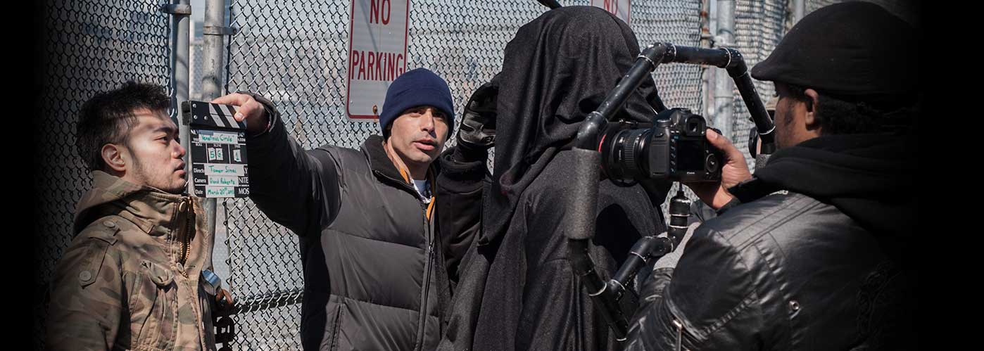 New York Film Academy student crew slates to film a scene in front of a chain-link fence.