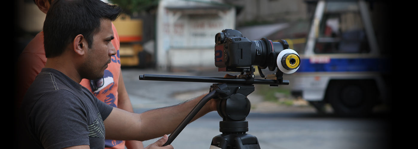 A NYFA student in a grey t-shirt directs his camera at a blurred vehicle and street background.