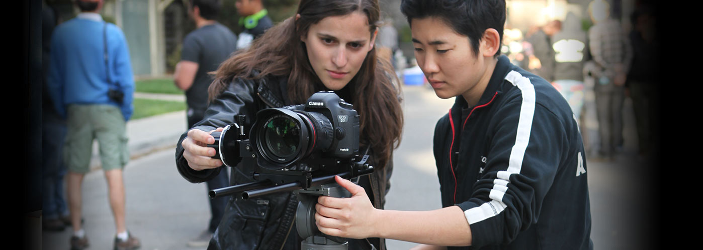 Two NYFA students work together to set up a shot with their mounted Canon camera.