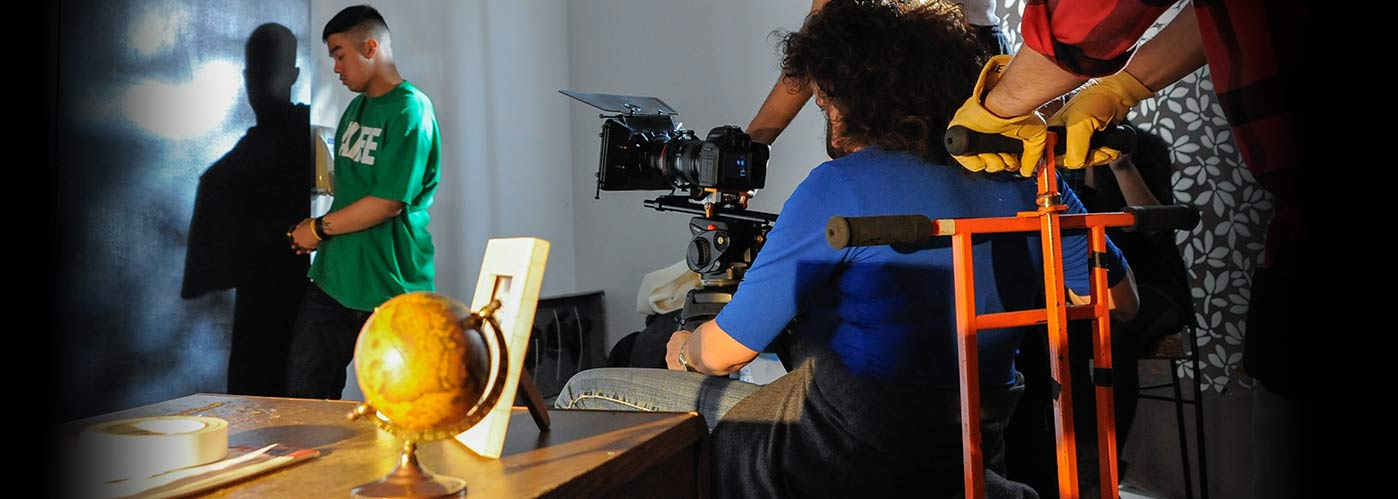 NYFA student director watches his actor as they shoot a scene behind a desk with a globe.