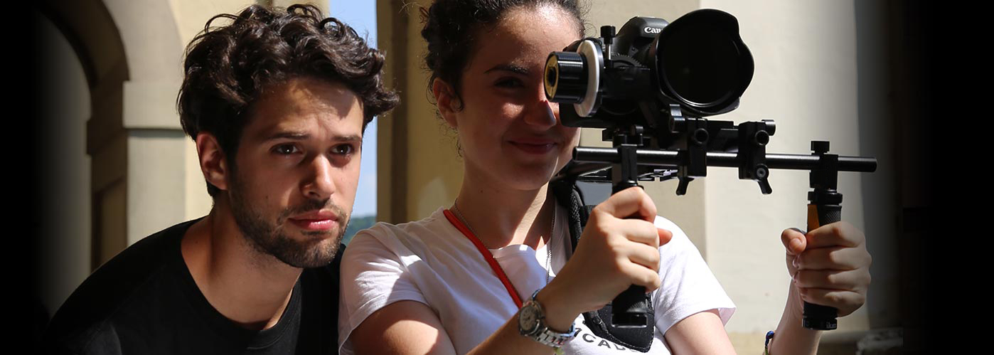 NYFA student director watches over his cinematographer's shoulder as she films with a steadicam.
