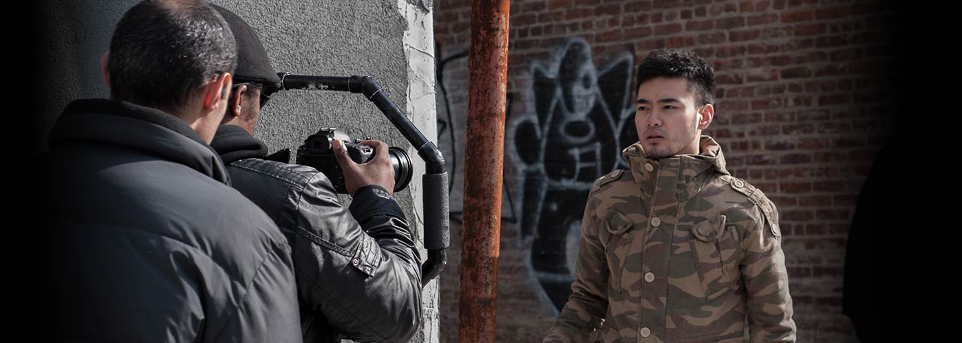 NYFA student directors film an actor in a camouflage jacket in a street scene outside a brick building.