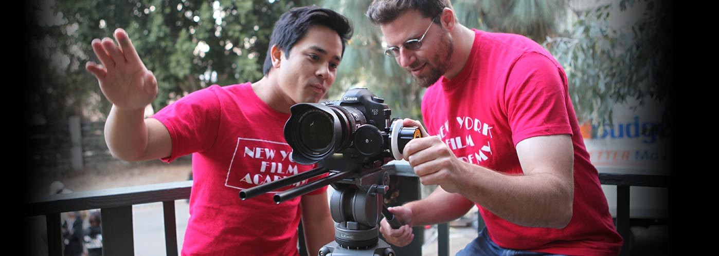 Two NYFA students in red NYFA t-shirts work together to set up an outdoor shot.