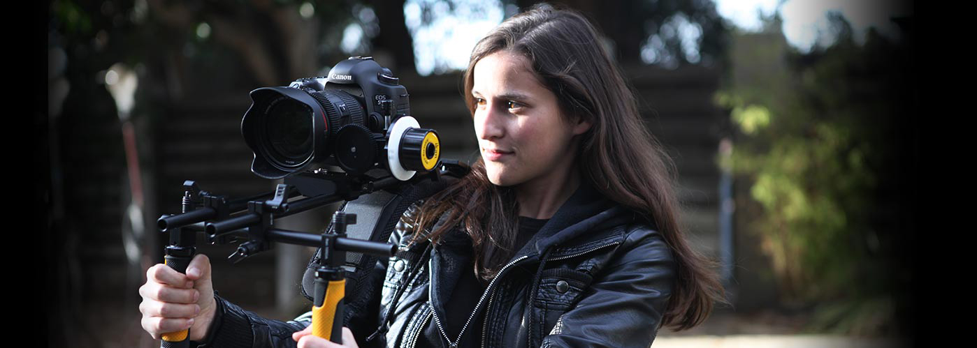 A female NYFA student with long brown hair works with a steadicam to capture her outdoor shot.