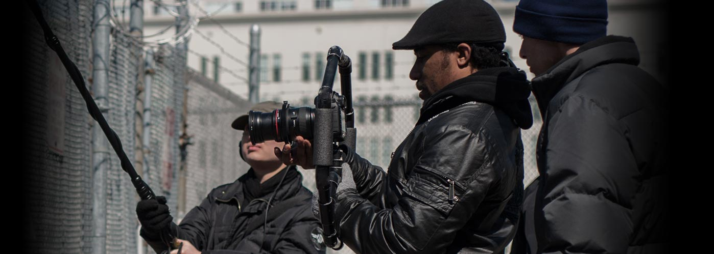 A NYFA student crew in black jackets and hats works with camera and sound equipment to capture an outdoor scene by a barbed wire fence.