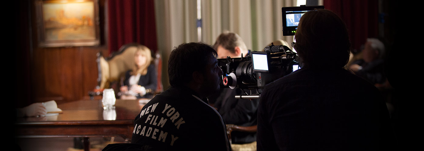 A NYFA student crew films an indoor scene in a richly colored room at a large wooden table.