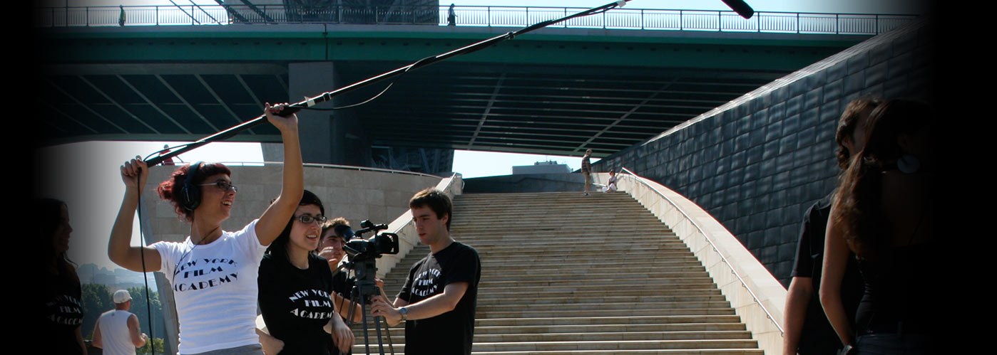 A NYFA student crew filming by a long outdoor staircase, with a female sound engineer holding up the boom.