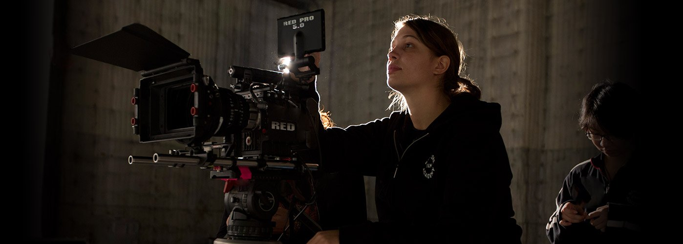 A female NYFA student director works with a RED camera on a sound stage.