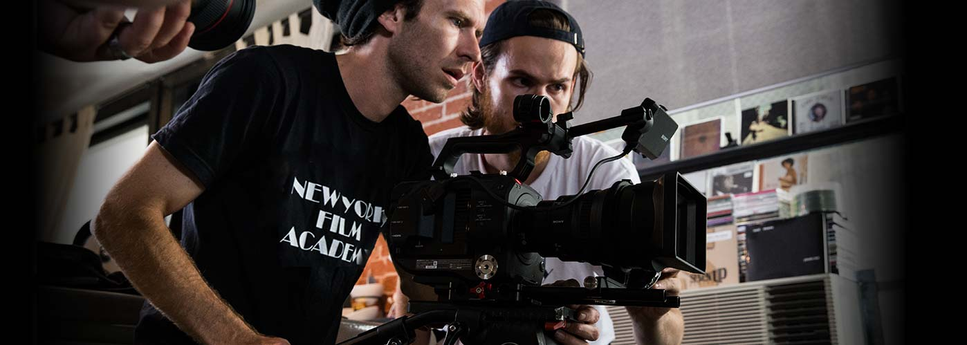 Two male NYFA students in black hats lean over their camera to inspect an indoor shot angle.