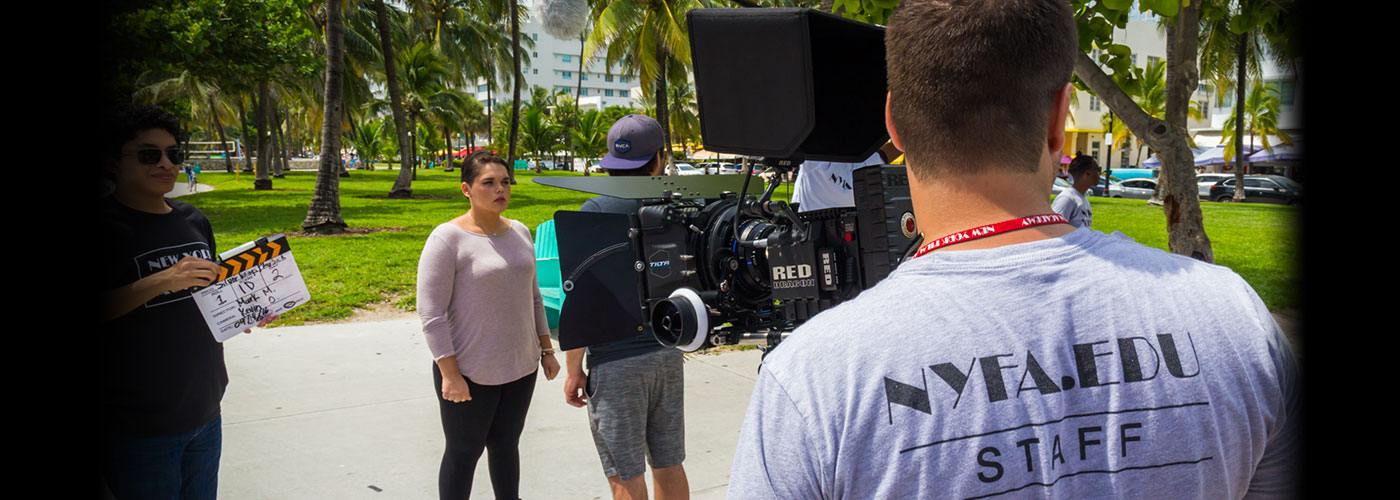 NYFA acting for film MFA students prepare for a take on set in a park filled with palm trees, as NYFA filmmaking students prepare their equipment.