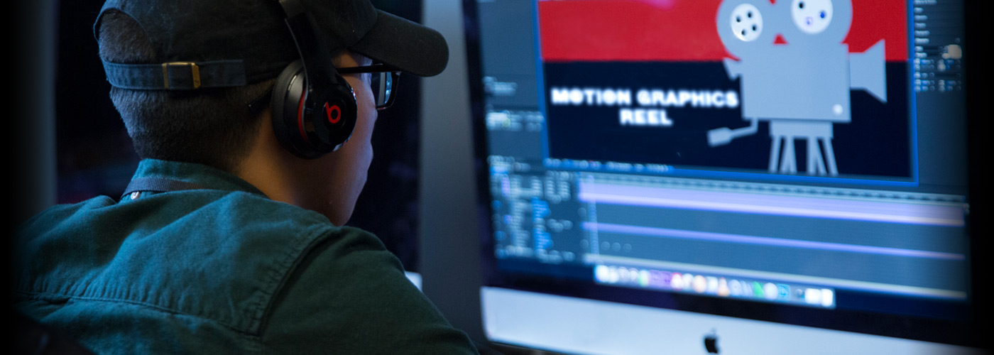A NYFA student in a baseball cap and glasses concentrates as he creates a motion graphic for an editor reel using After Effects.