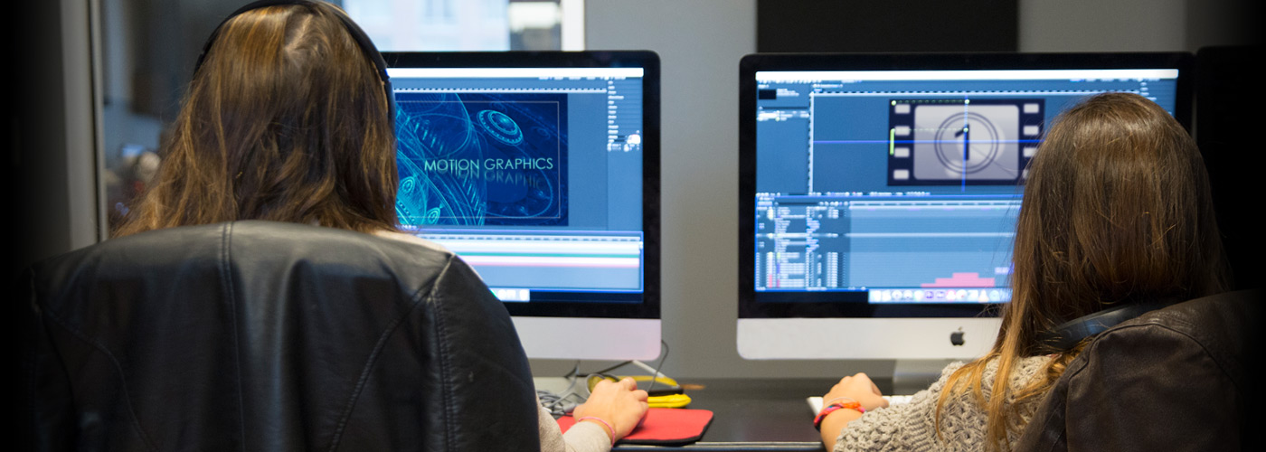 An over-the-shoulder view as two NYFA students with long hair concentrate on their motion graphics projects at their in-class workstations.