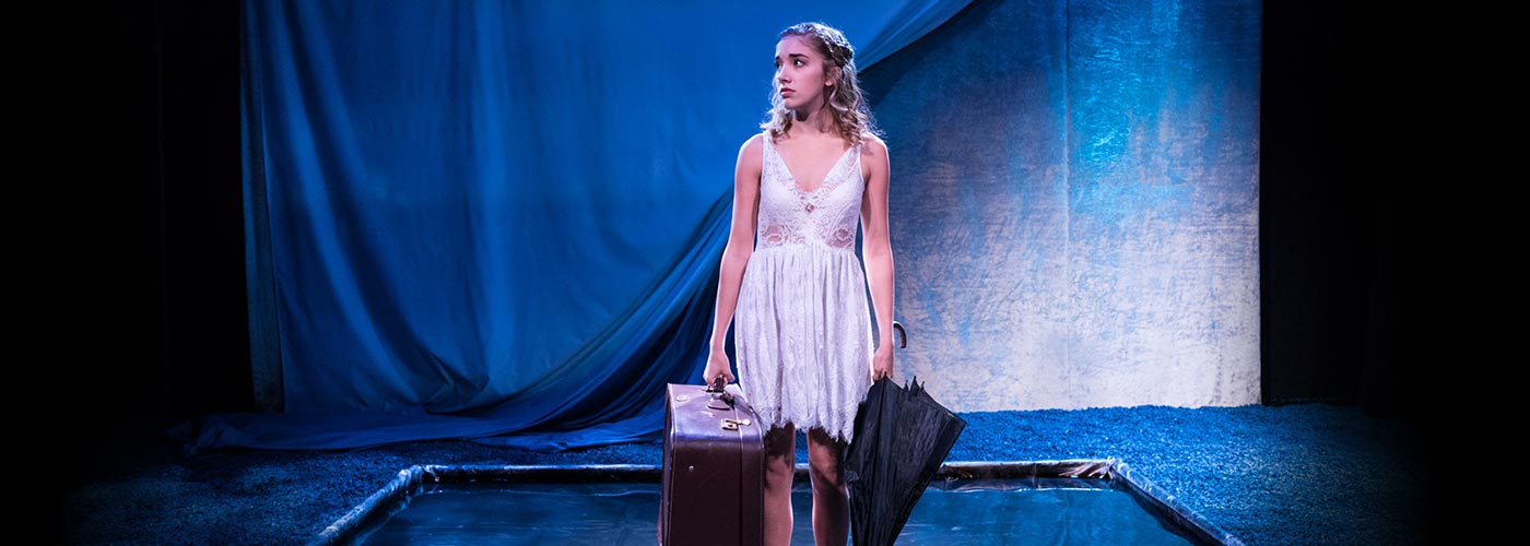 NYFA musical theatre student as Eurydice performs onstage with a suitcase and umbrella.