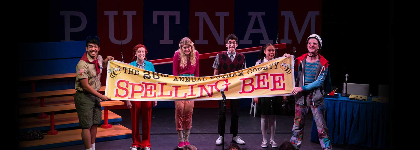 NYFA musical theatre student ensemble holds up the sign for The 25th Annual Putnam County Spelling Bee.