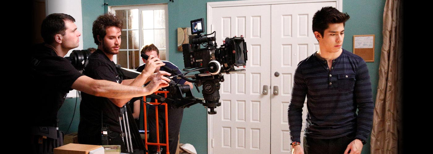 NYFA filmmaking students concentrate while filming an acting student's performance in a room with teal walls.