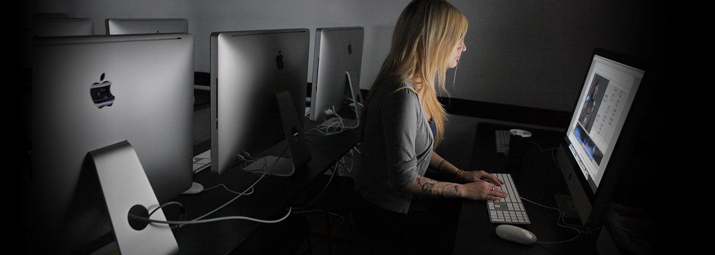New York Film Academy photography student with tattoos works on post production in lab.