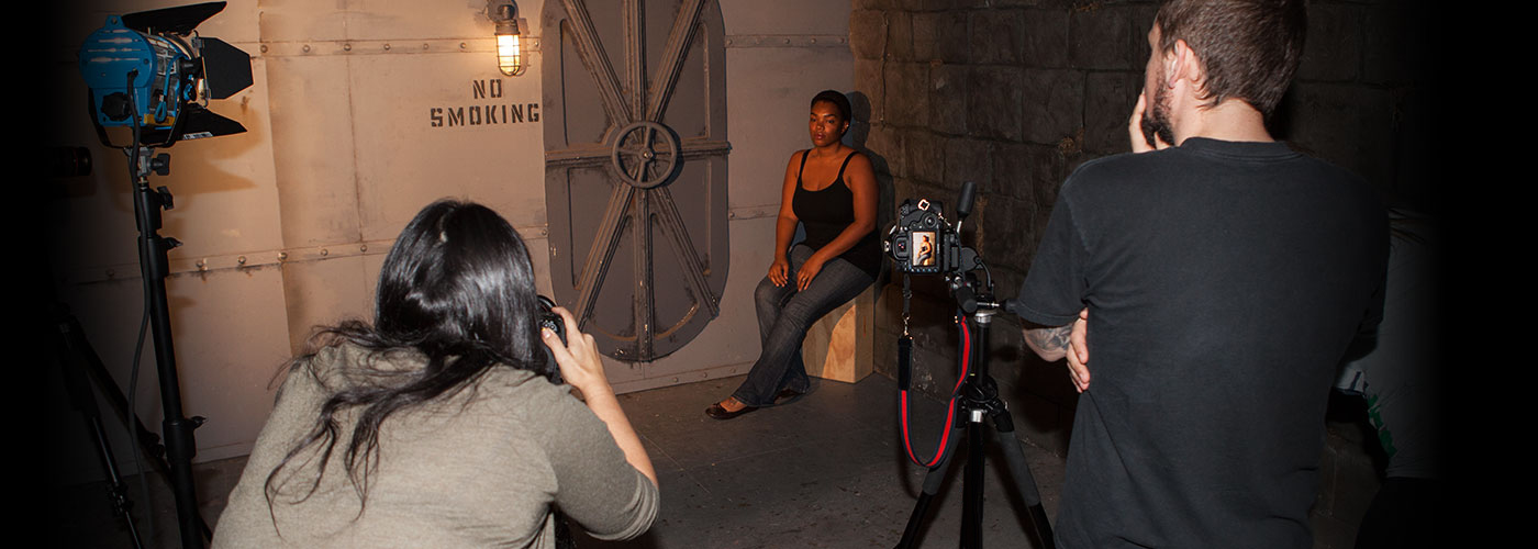 New York Film Academy photography students work with a model on set inside a metal bunker.
