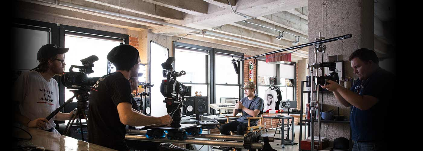 New York Film Academy producing students filming with two cameras on location in a warehouse.
