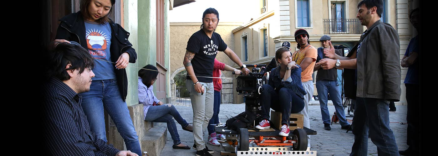 9 NYFA producing students work together to measure a shot from a dolly on an outdoor set.