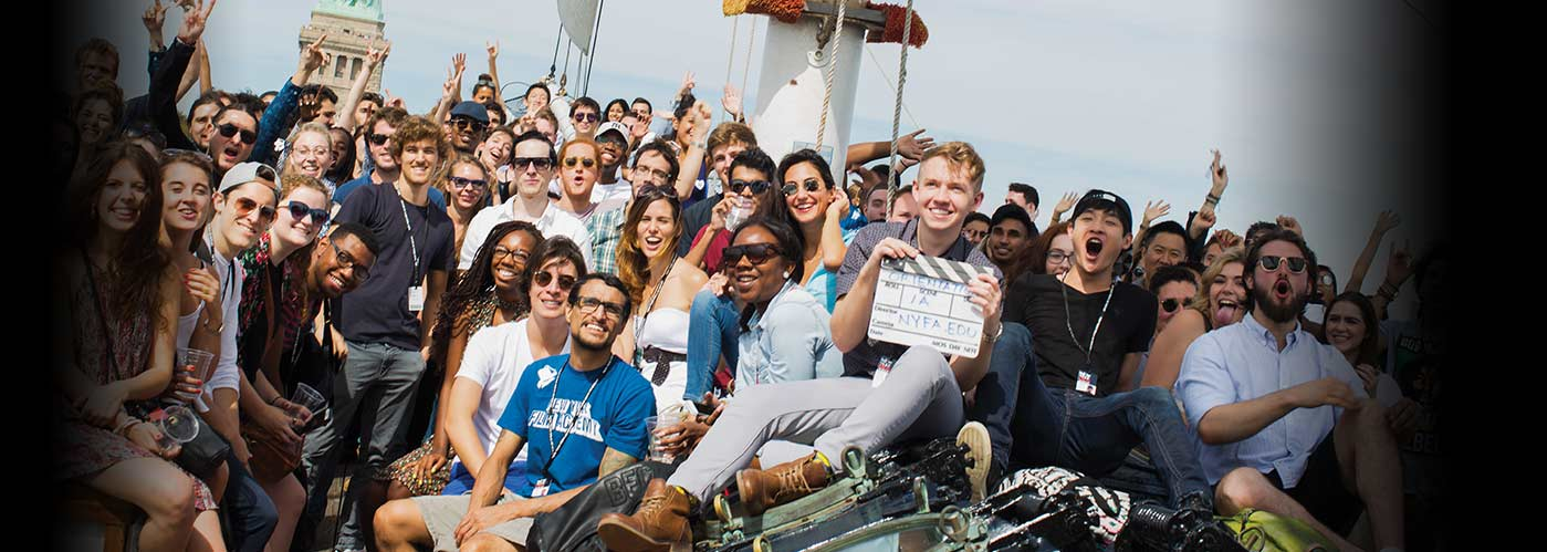 A large New York Film Academy class poses for a photo on a ship approaching the Statue of Liberty.