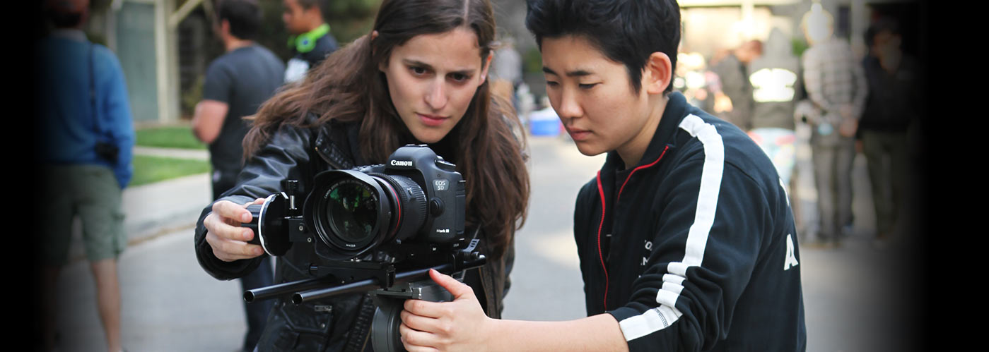 Two New York Film Academy students concentrate as they work together to set up their Canon camera for a shot.