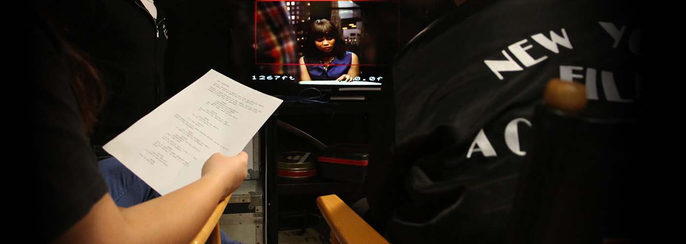 NYFA screenwriting student working on set as a script supervisor, while director watches monitor.