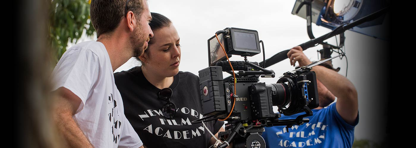 Two NYFA special projects students concentrate on their shot through a Red camera.
