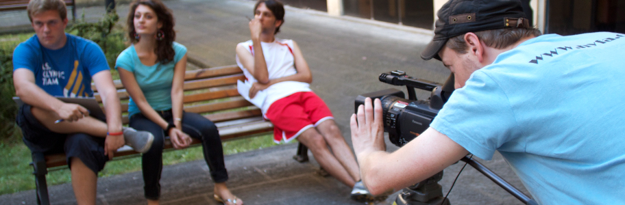 Broadcast journalism student films subjects sitting on a park bench