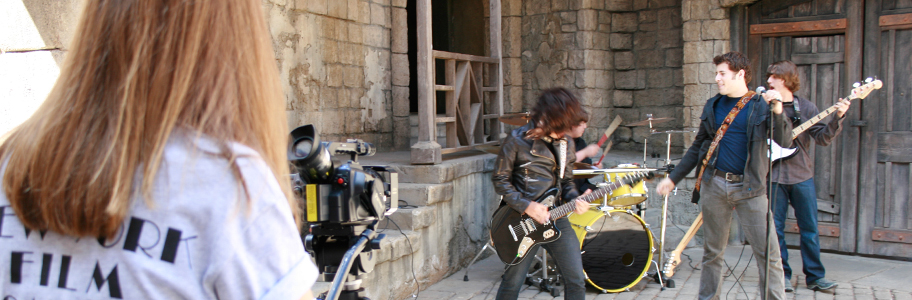A rock band performs as a student films a music video