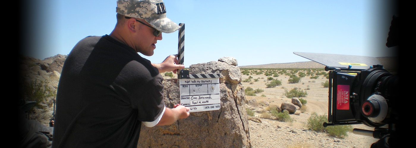 A veteran student holds a clapboard on set