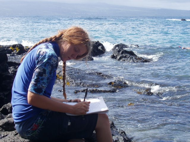 Young woman writing in her journal at the beach