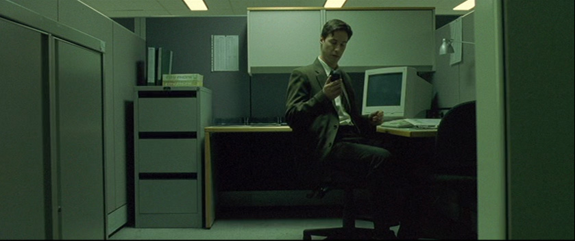Neo in his cubicle in The Matrix