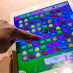 finger playing candy crush on iPad