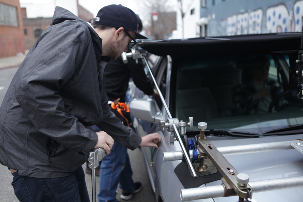 Crew member setting up car camera rig