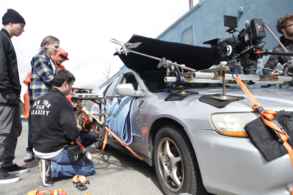 Crew members adjusting car camera rig