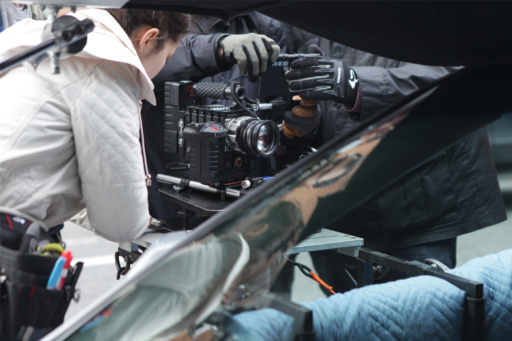 Crew members setting up camera on car rig