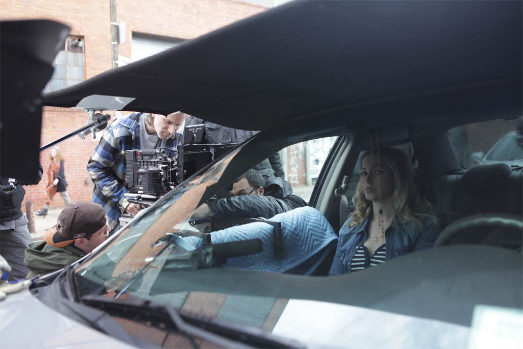 Crew members adjusting car camera rig while actress waits in the car