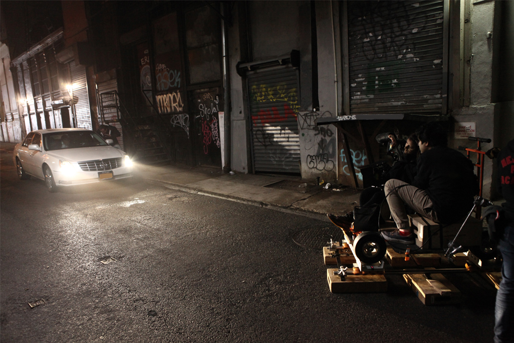 Two men in an alley filming a white car at night