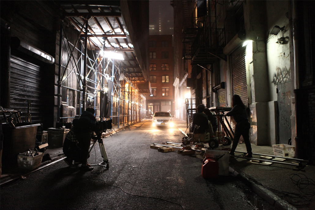 People filming a car in an alley at night