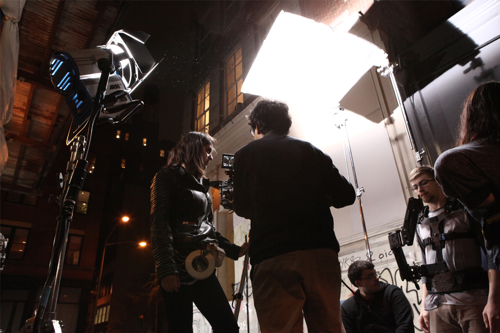 A camera crew reviewing footage in an alley