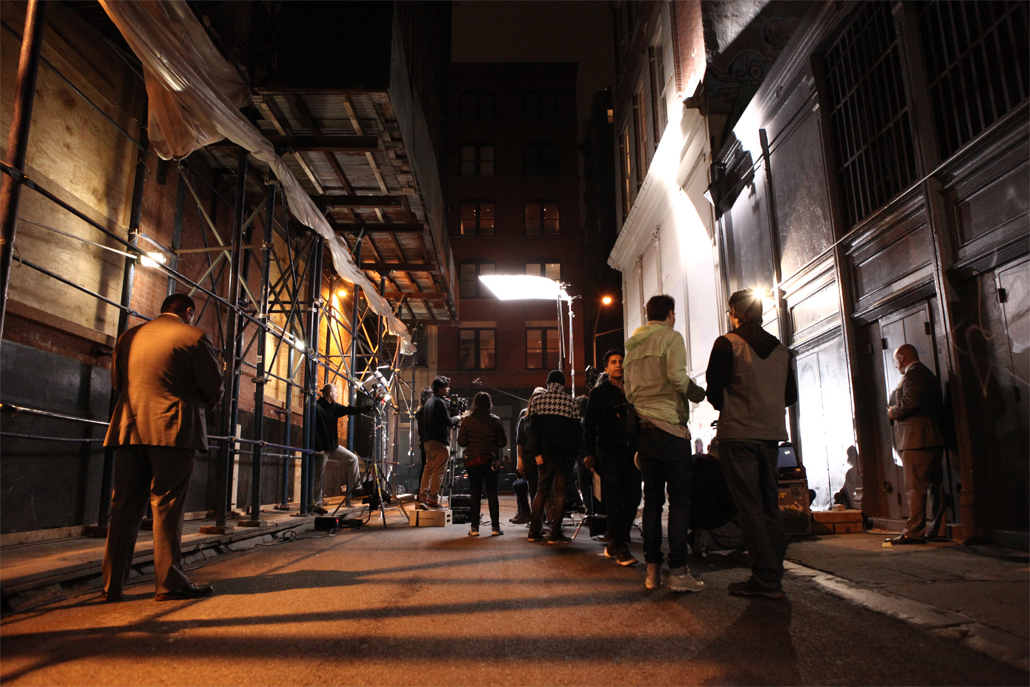 Several people in an alley filming at night