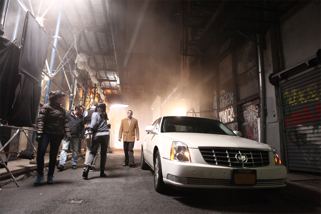 A white cadillac car in an alley with people around it