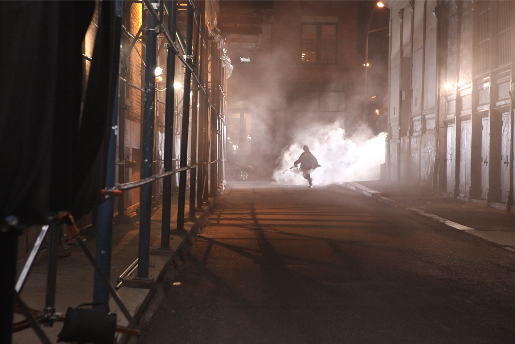 Crew member using fog machine and running down an alley