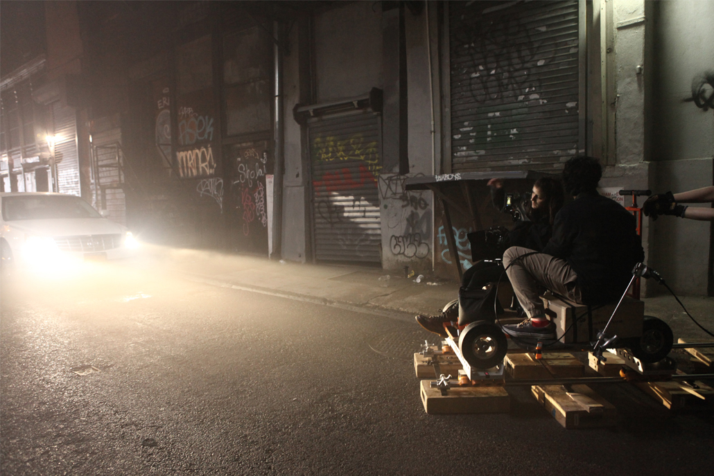 Two men in an alley filming a car with bright headlights at night