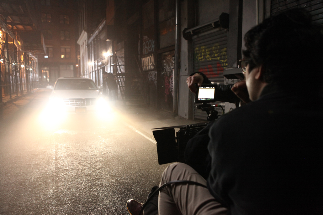 One man and a camera filming a car at night