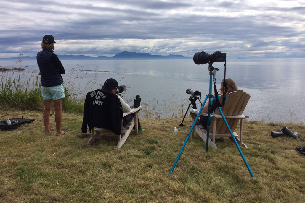 People sitting in chairs looking out at ocean with film equipment