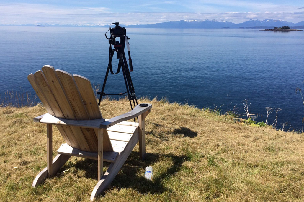 Wooden lounge chair with camera facing ocean and mountains