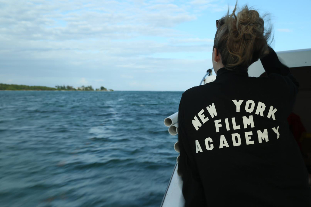 Woman on boat with 'New York Film Academy' written on back of jacket