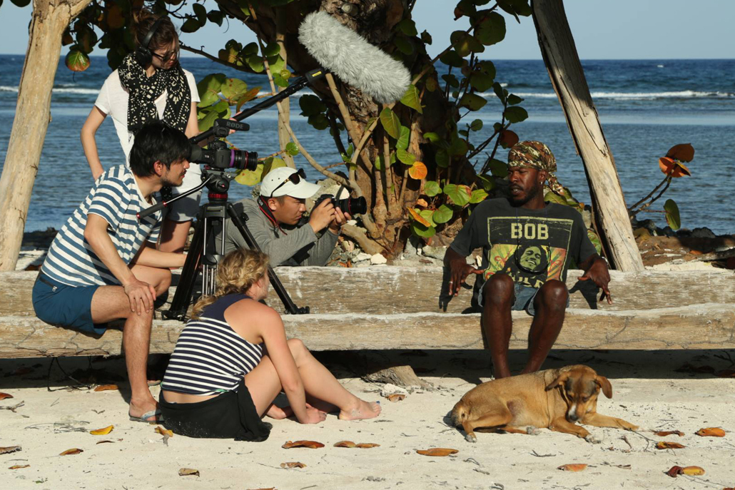 Film crew interviewing man on beach with dog