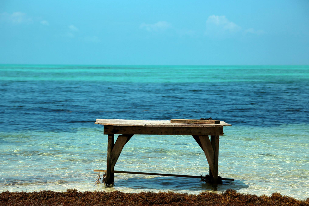Wooden table sitting in shallow part of ocean shore